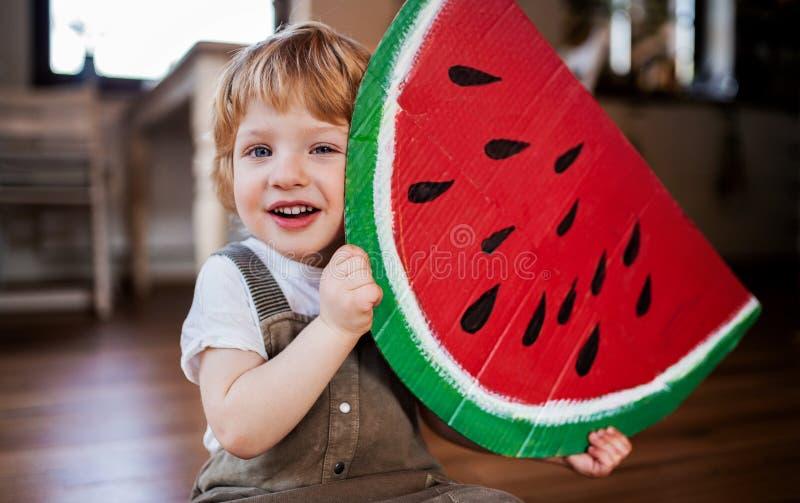 Um menino da criança que joga com grande fruto do brinquedo dentro em casa fotografia de stock