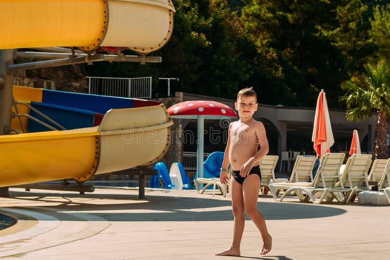 Um menino de 6 anos bem-alimentado em troncos de natação anda no território do hotel em Turquia Verão ensolarado fotos de stock royalty free