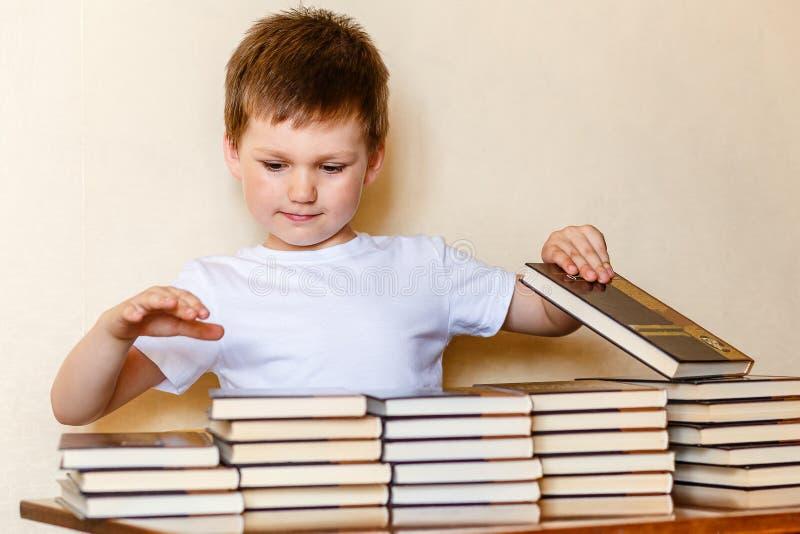 Um menino de 6 anos bonito senta-se em uma mesa e põe-se livros sobre pilhas foto de stock royalty free