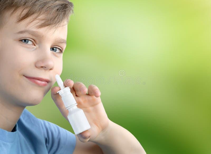 Um menino de doze anos de pulverizador nasal dos pulverizadores velhos em um fundo borrado verde fotos de stock