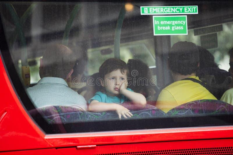Um menino de quatro olhares no vidro traseiro de um ônibus foto de stock royalty free