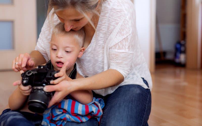 Um menino de Síndrome de Down e sua mãe com uma câmara digital dentro foto de stock royalty free