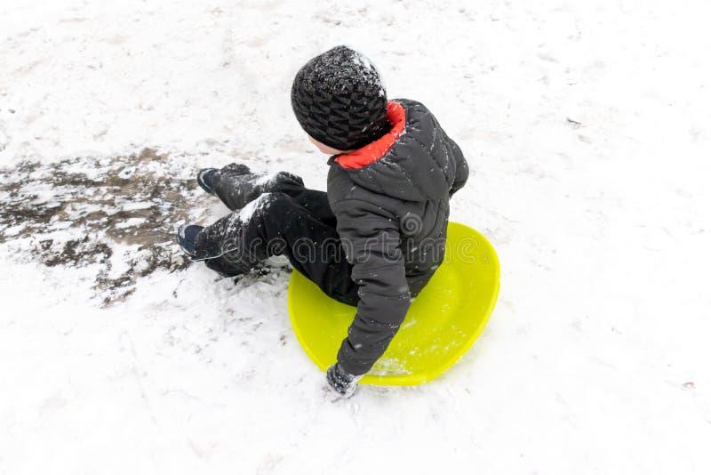 Um menino de sete anos velho monta a corrediça, abaixo do monte no trenó verde do gelo Conceito de atividades, de recreação e de  imagens de stock