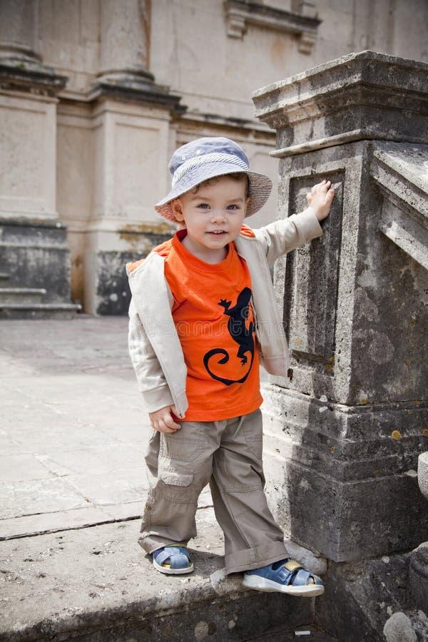 Um menino de sorriso bonito pequeno em um t-shirt alaranjado e em um chapéu azul está em uma escadaria velha O quadro vertical imagens de stock royalty free