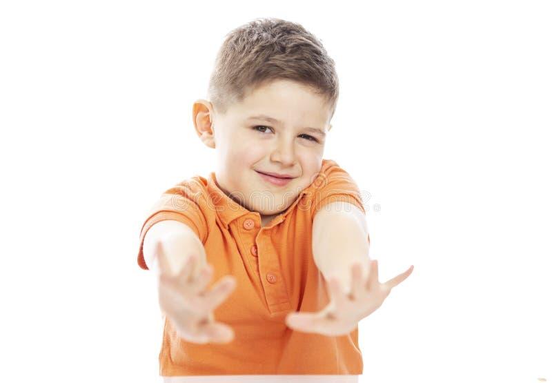 Um menino de sorriso da idade escolar em um t-shirt alaranjado brilhante do polo senta-se em uma tabela, braços estendeu para a f foto de stock royalty free