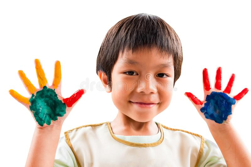 Um menino do jardim de infância do sorriso tem o divertimento para pintar sua mão com cores fotos de stock