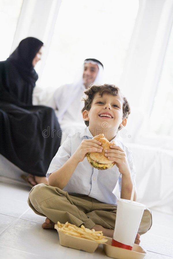 Um menino do Oriente Médio que aprecia o fast food fotografia de stock royalty free