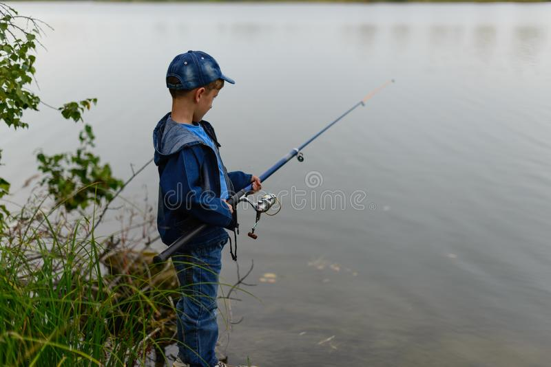 Um menino do pescador no banco de rio com uma vara de pesca em sua mão foto de stock