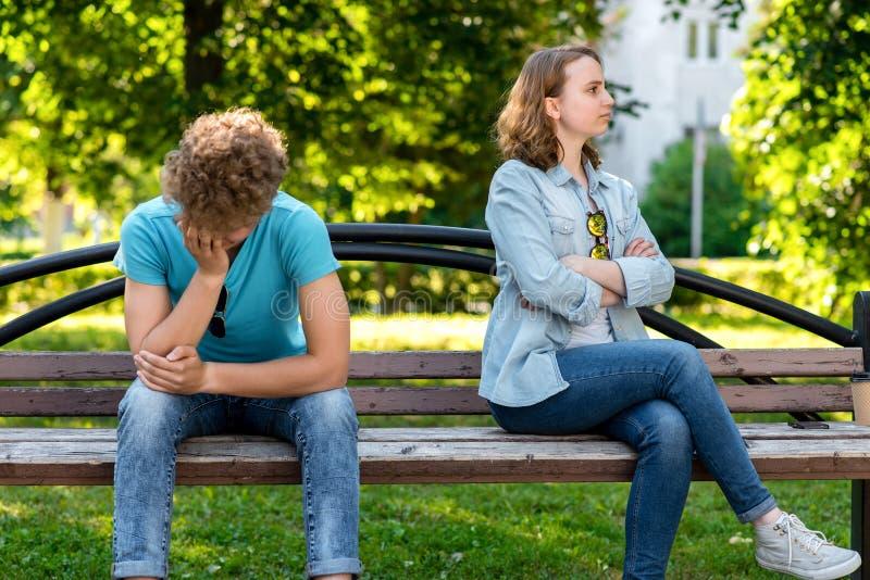 Um menino e um banco de assento da menina No verão no parque na natureza O ressentimento do conceito do engano Discussão na imagens de stock