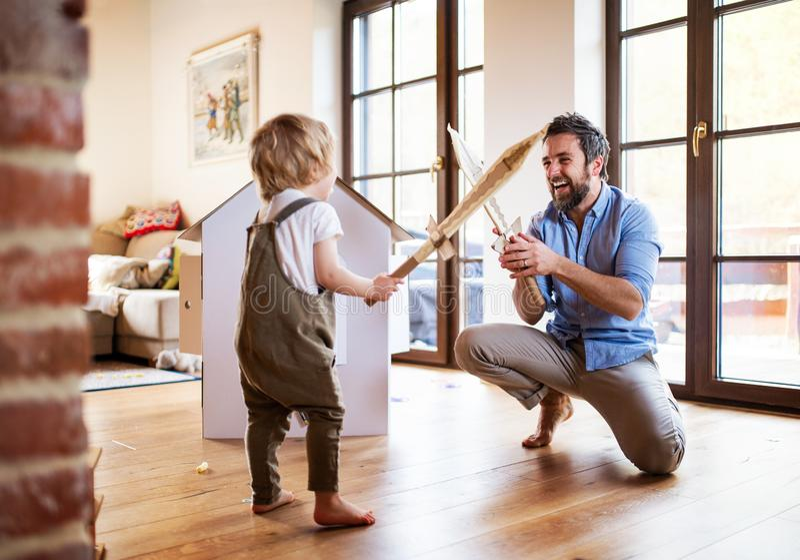 Um menino e um pai da criança com as espadas da caixa que jogam dentro em casa foto de stock