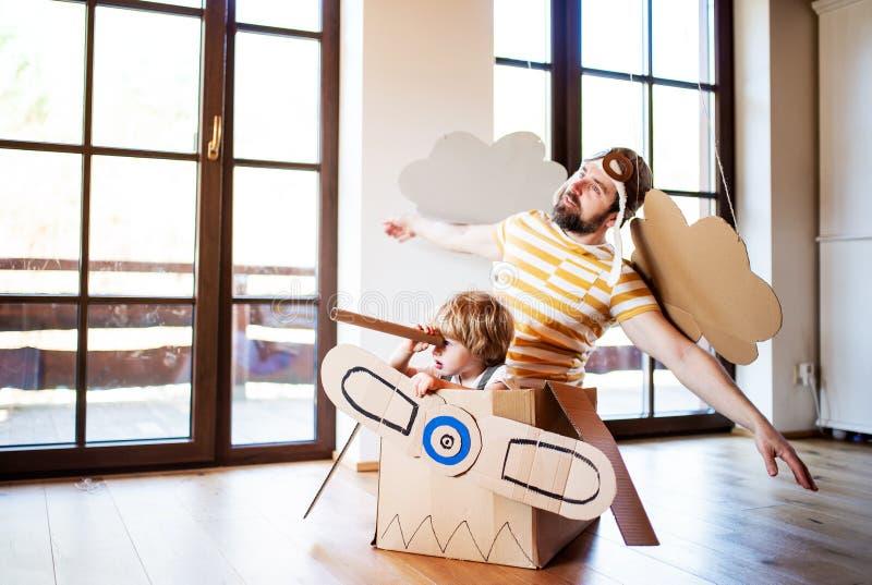 Um menino e um pai da criança com o plano da caixa que joga dentro em casa, conceito de voo imagem de stock royalty free