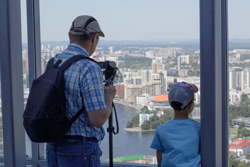 Um menino e seu avô que olham de uma janela panorâmico de um prédio na cidade de Yekaterinburg imagens de stock royalty free