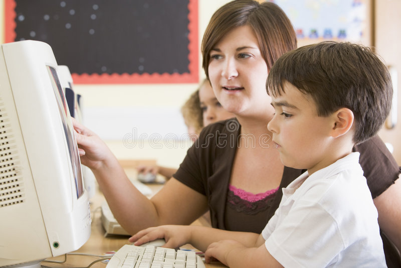Um menino e seu professor que trabalham em um computador foto de stock