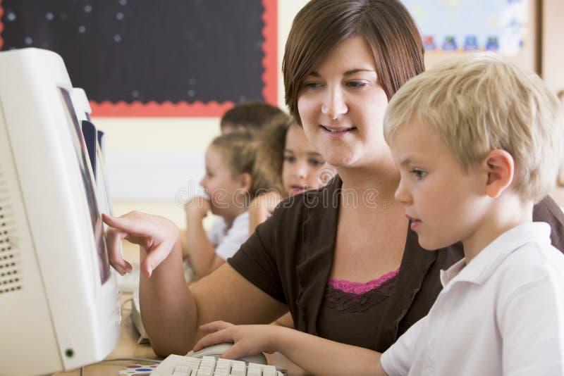 Um menino e seu professor que trabalham em um computador. foto de stock royalty free