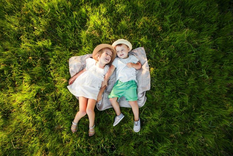 Um menino e uma menina estão encontrando-se na grama verde Vista superior Espaço para o texto imagem de stock