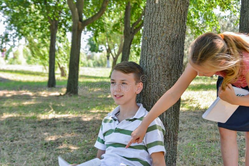 Um menino e uma menina para fazer seus trabalhos de casa no parque e para preparar-se junto para a escola foto de stock