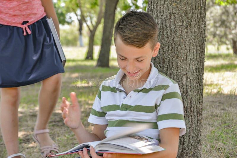 Um menino e uma menina para fazer seus trabalhos de casa no parque e para preparar-se junto para a escola fotos de stock