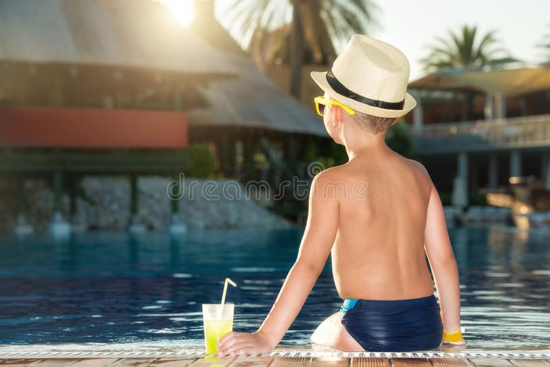 Um menino em um chapéu de palha com um cocktail à disposição que senta-se na associação fotografia de stock