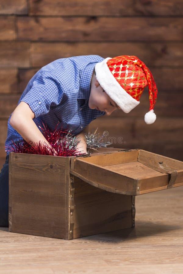 Um menino em um chapéu de Santa Claus, nas calças de brim, em uma camisa azul, abre uma caixa de madeira com decorações do Natal  foto de stock royalty free