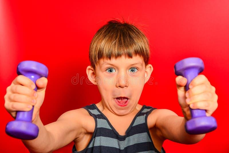 Um menino em um t-shirt listrado vai dentro para esportes com pesos roxos em um fundo vermelho foto de stock royalty free