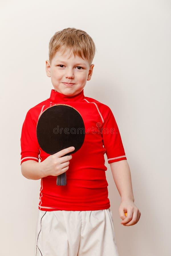 Um menino em um t-shirt vermelho que guarda uma raquete para o tênis de mesa imagens de stock royalty free