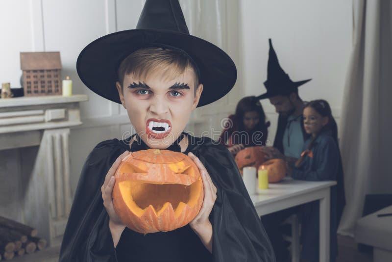 Um menino em um terno do vampiro está guardando uma abóbora assustador para Dia das Bruxas foto de stock royalty free
