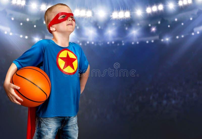 Um menino em um traje do super-herói joga o basquetebol fotografia de stock