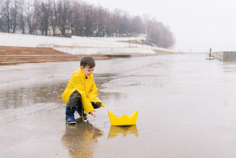 Um menino em uma capa de chuva do amarelo joga e lança em uma poça um brinquedo do barco do grande papel fotos de stock