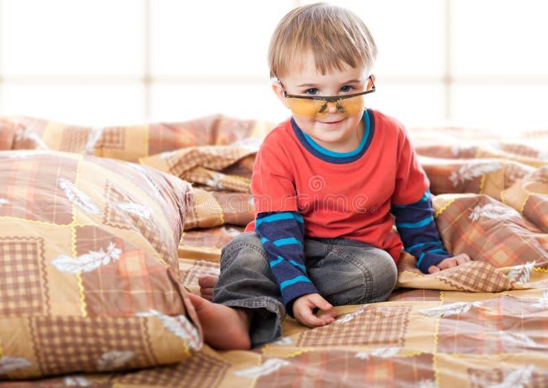 Um menino em vidros engraçados na cama fotografia de stock