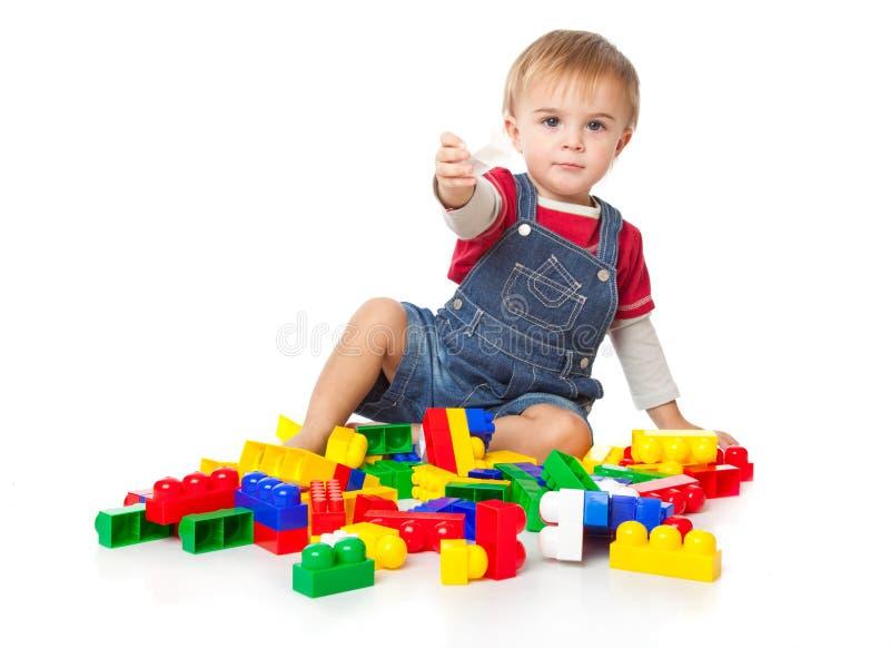Um menino engraçado está jogando com lego fotografia de stock royalty free