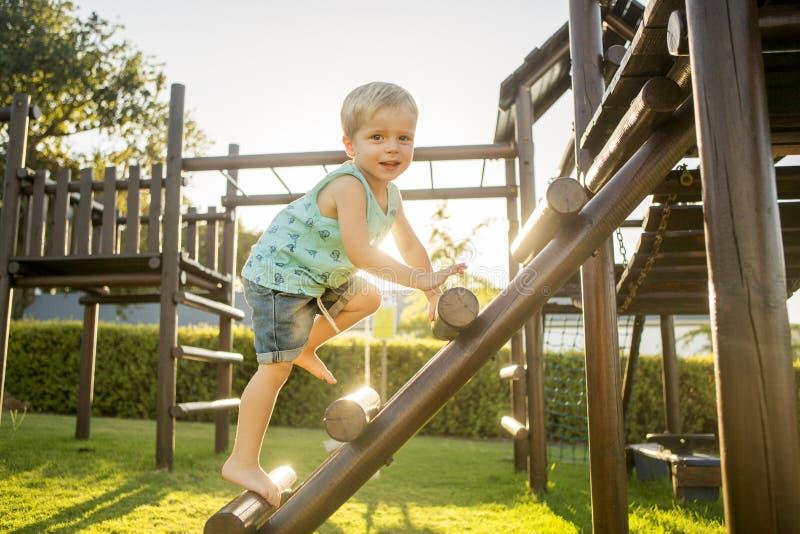 Um menino escala um Gym de selva em Sunny Green Park fotografia de stock