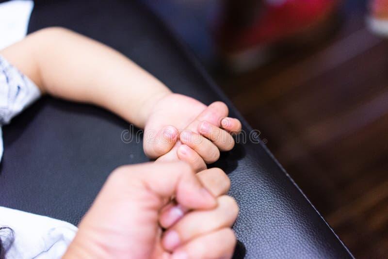 Um menino está guardando seu dedo do pai para mostrar sua confiança e acredita-o imagem de stock
