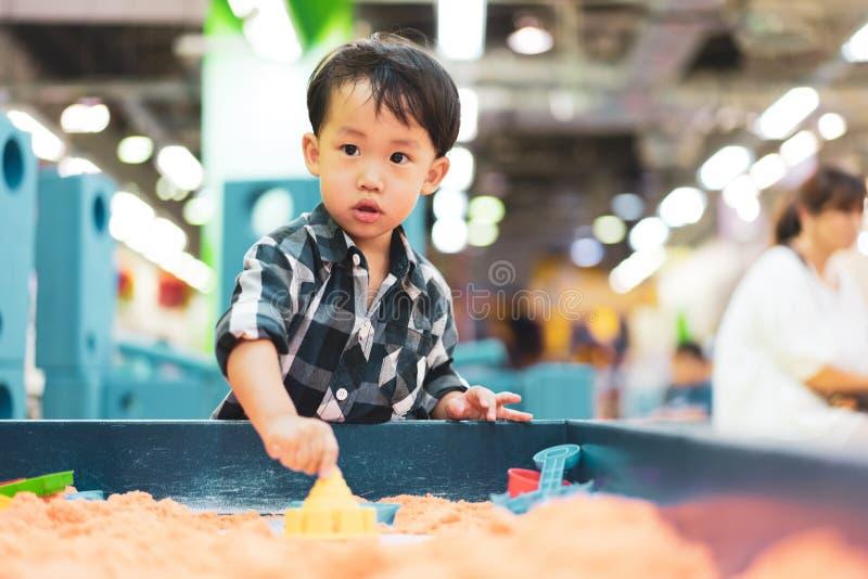 Um menino está jogando a areia da ciência no campo de jogos imagem de stock