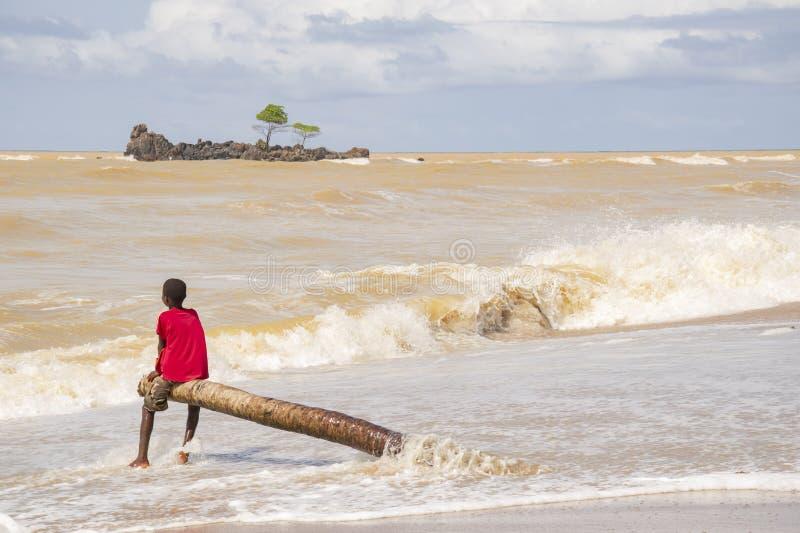Um menino está jogando com o mar fotos de stock