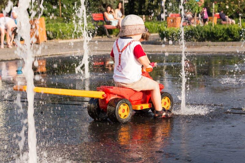 Um menino está jogando na fonte da cidade no tempo quente imagens de stock royalty free