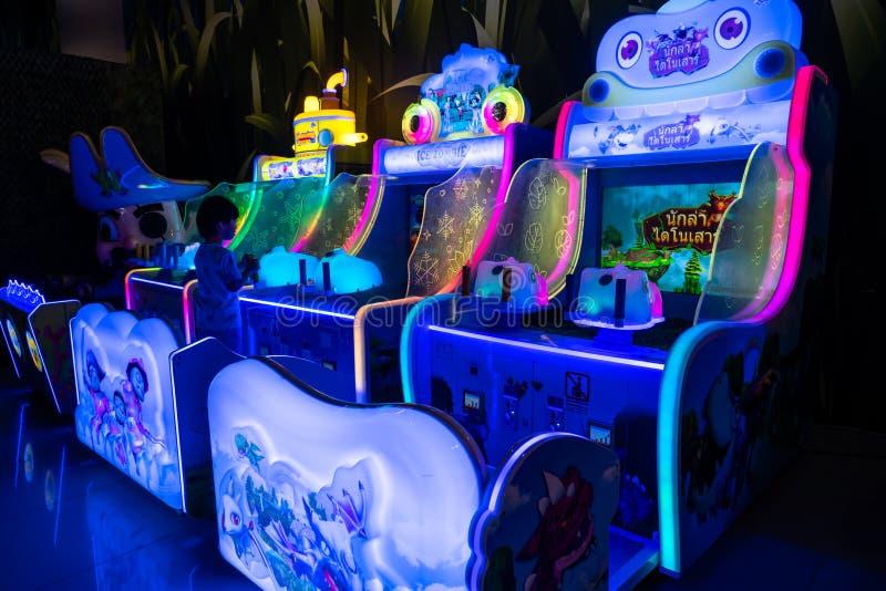 Um menino está jogando o jogo de vídeo em um centro de jogo com os armários coloridos do jogo no armazém foto de stock