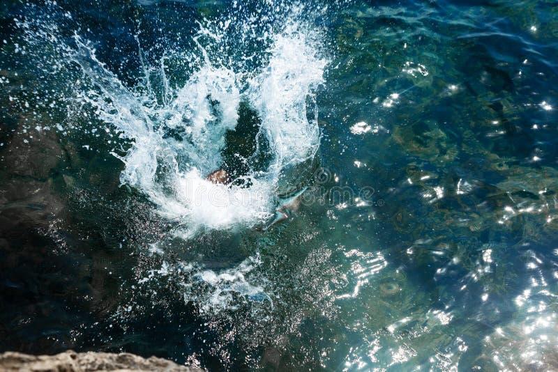 Um menino está saltando do penhasco no mar com respingo grande da água em um dia de verão quente Feriados na praia E imagens de stock royalty free