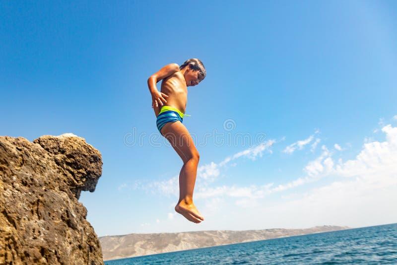 Um menino está saltando do penhasco no mar em um dia de verão quente Feriados na praia O conceito do turismo ativo fotos de stock royalty free