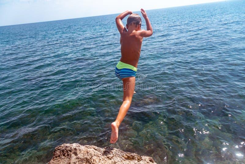 Um menino está saltando do penhasco no mar em um dia de verão quente Feriados na praia O conceito do turismo ativo foto de stock