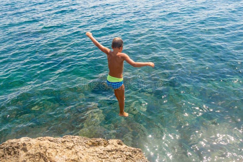 Um menino está saltando do penhasco no mar em um dia de verão quente Feriados na praia O conceito do turismo ativo fotografia de stock