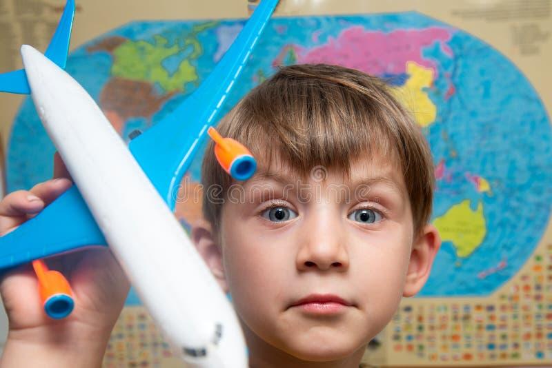 Um menino feliz e alegre está guardando um avião na perspectiva do atlas do mundo, do turismo e do curso fotografia de stock royalty free