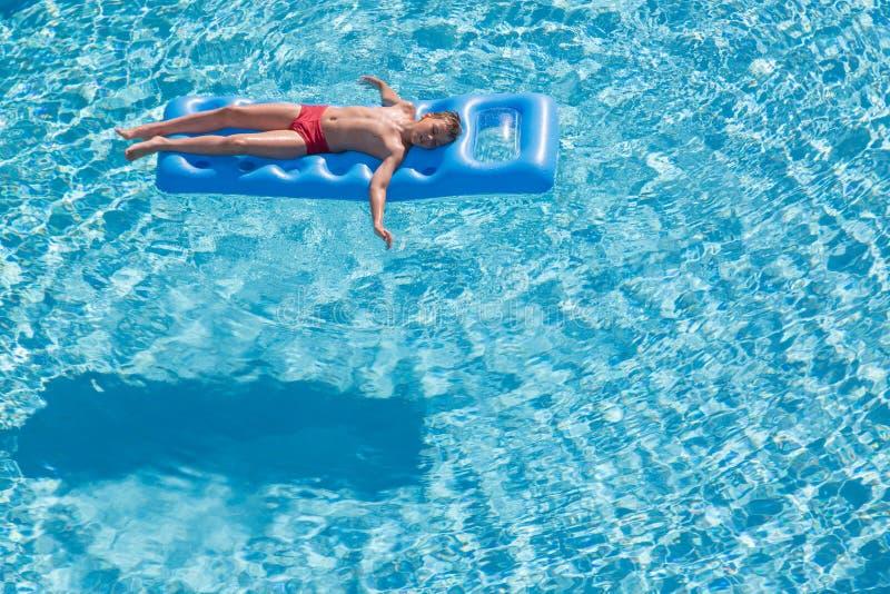 Um menino flutua em um colchão inflável imagens de stock royalty free