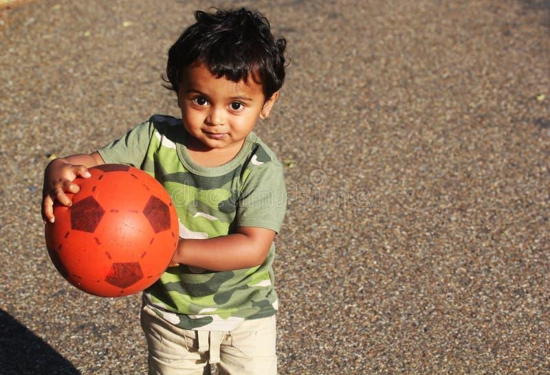 Um menino indiano novo que joga com uma bola vermelha imagens de stock