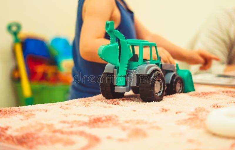 Um menino joga com um trator fotografia de stock
