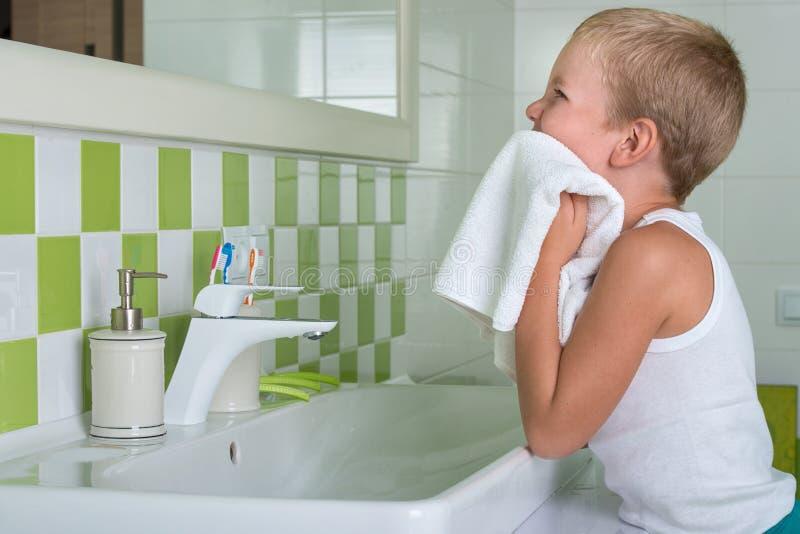 Um menino lava sua cara, limpa sua cara com uma toalha no banheiro fotos de stock