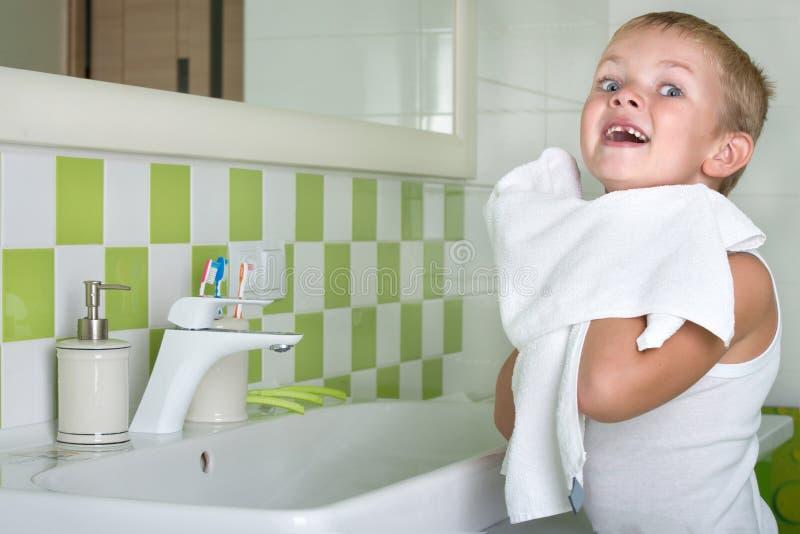 Um menino lava sua cara, limpa sua cara com uma toalha no banheiro imagem de stock royalty free
