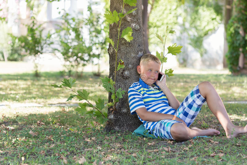 Um menino louro que fala em seu telefone celular imagens de stock
