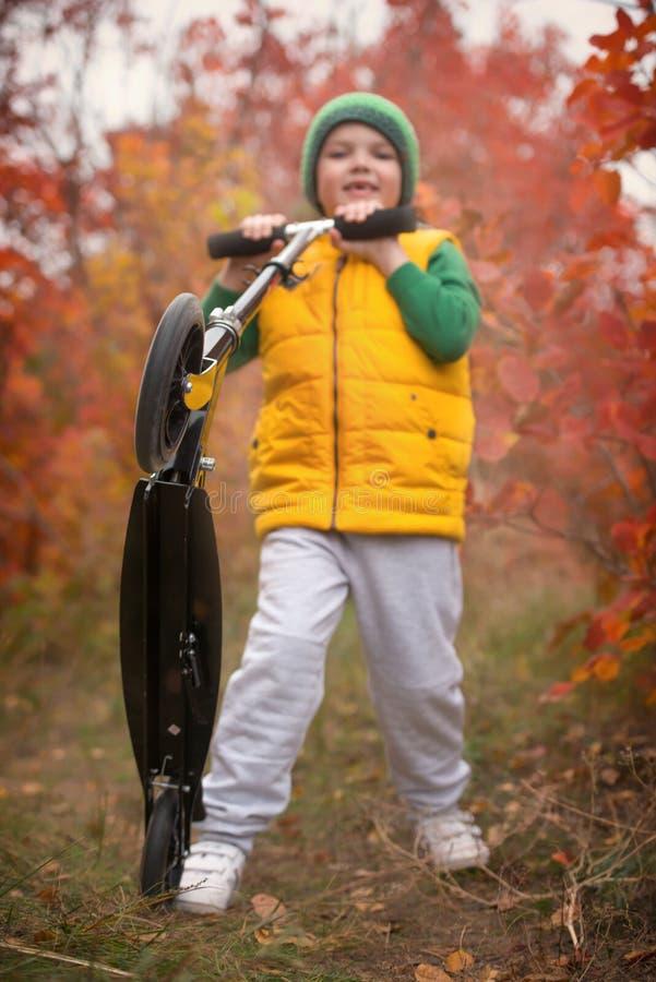 Um menino monta um 'trotinette' no parque do outono imagem de stock