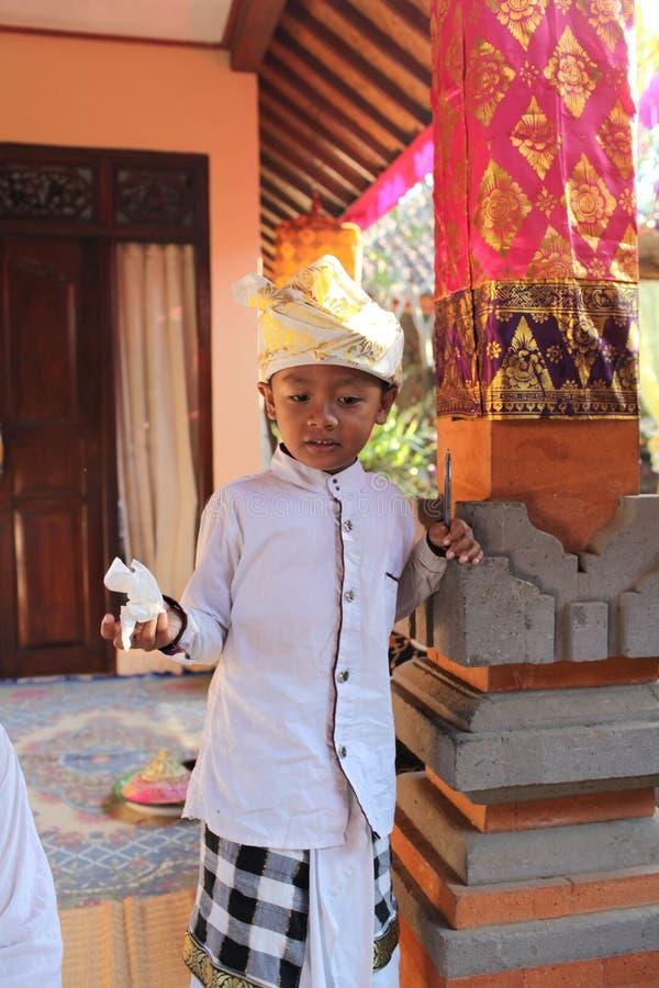 Um menino muito pequeno do Balinese decorou devido à cerimônia de Potong Gigi - dentes do corte, ilha de Bali, Indonésia imagens de stock