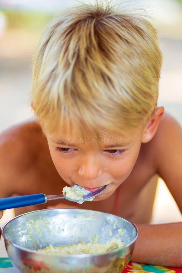 Um menino na natureza come o papa de aveia imagens de stock
